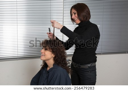 A woman with hair curlers rollers by hairdresser in  beauty salon