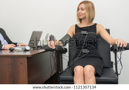 A woman with hair, dressed in a black dress, printing instruments are present on the table