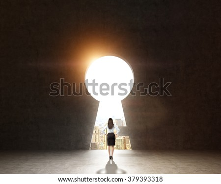 A woman with hands on hips standing in front of a huge keyhole, city and sky seen through it. Black background. Back view.  Concept of finding the way Foto stock ©