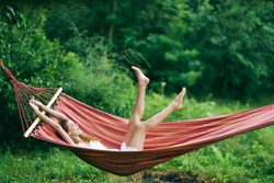 A woman with her arms and legs up is lying in a hammock in nature