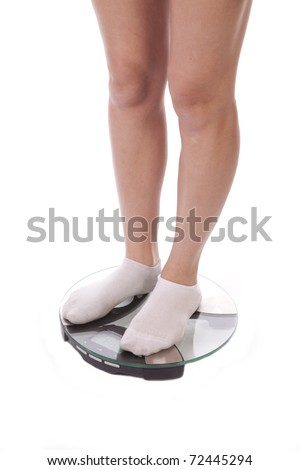 A woman with her legs on the bathroom scales, wearing socks.