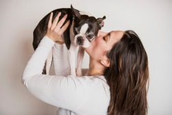 A woman with is Boston Terrier on studio white background