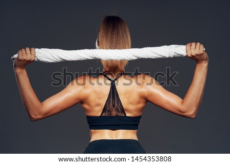 A woman with muscled muscles holds a towel over her head a short tank top sport leggings
