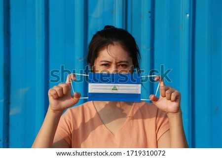 Photo of  A woman with Nicaragua flag on hygienic mask in her hand and lifted up the front face on blue background. Tiny Particle or virus corona or Covid 19 protection. Concept of Combating illness.