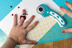 A woman with orange nail polish cut her finger with a rotary cutter while using a bright blue cutting mat and a ruler