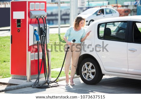 A woman with phone stands at the charging station and holds a plug of the charger for an electric car #1073637515