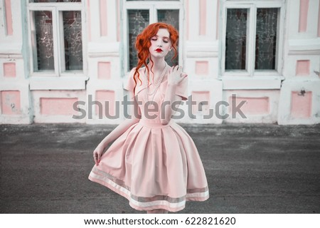 A woman with red curly hair in a peach dress on background vintage window. Red-haired girl with pale skin, blue eyes, a bright unusual appearance and red lips and a thin waist with beads on her neck