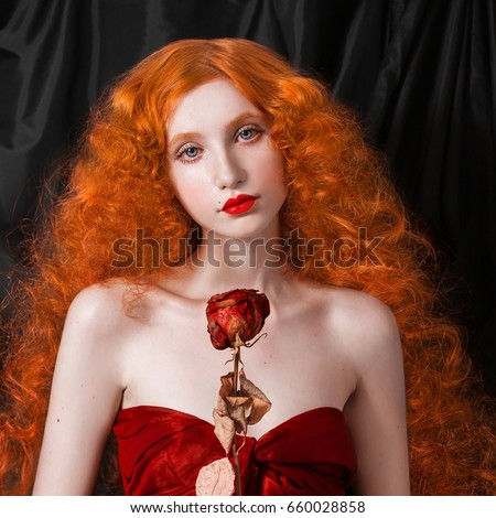 Stock Photo A woman with red hair in a red fitting long dress with dry rose in hand on black background. Red-haired girl with pale skin and blue eyes with a bright unusual appearance. Pin-up woman