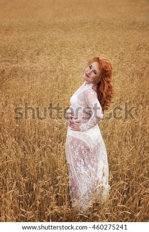 A woman with red hair in a wheat field. Portrait of a Woman in nature #460275241
