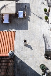 A woman with textiles crosses a gray paving square. View from above. European houses, red roof tiles, cafes, restaurants. Tables under a canopy on the street.