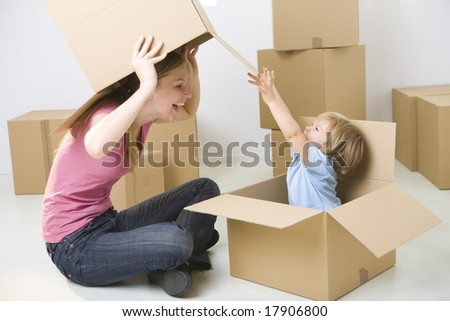 A woman with young girl sitting between cardboard boxes. Happy woman holding box over head and looking at young girl. Young girl sitting in box.