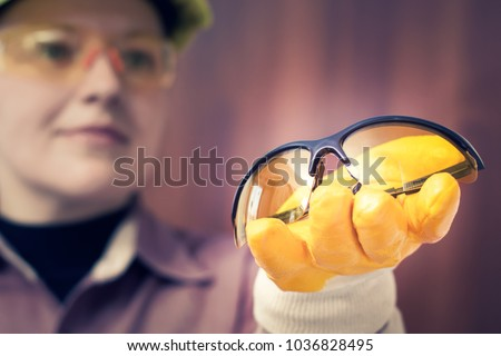 A woman worker offers safety glasses
