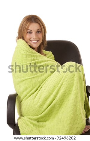 A woman wrapped up in a lime green blanket in a chair with a smile on her face.