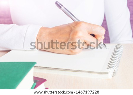 A woman writes in a notebook with a pen. She is wearing a white long-sleeved T-shirt. The concept of training, homework, writing a business plan, making a to-do list.