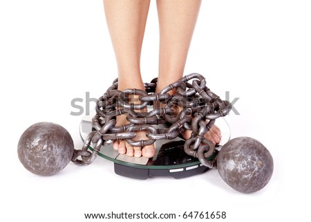 A womans feet are chained to the scales