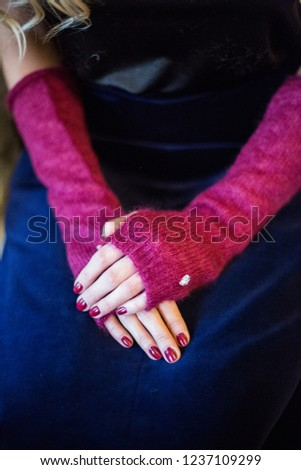A womans hands in burgundy colour mohair hand warmers with Swarovski crystal decoration on navy blue velvet skirts