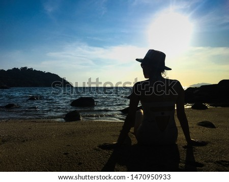 A women sits on the seashore against a beautiful sunset. Evening relaxing relaxing in the wild