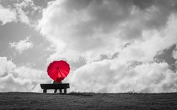 a women sitting alone on a bench with a red heart shaped umbrella waiting for love