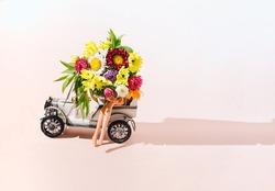 A women sitting in an old timer with a bunch of various beautiful colorful flowers, bare legs visible. Wedding or other special occasion invitation creative concept. Surreal romantic artsy concept