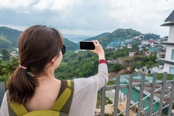 a women traveller taking photo of beautiful mountain view by their phone