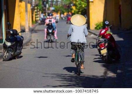 "A women wearing ""Non La"", Vietnam traditional hat made by coconut leaf. She ride her bicycle along the street inside Hoi An ancient town, Hoi An is a popular tourist destination of Asia, Vietnam #1007418745"