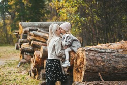 A wonderful mother kissing her small daughter against the background of stacked logs on background in a autumn forest. Horizontal view
