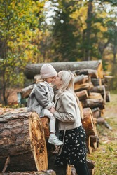 A wonderful mother kissing her small daughter against the background of stacked logs on background in a autumn forest. Lifestyle concept. Nature concept.