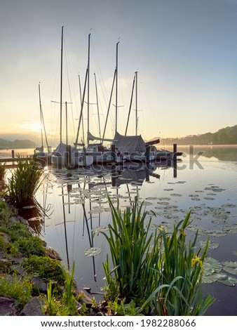 A wonderful sunrise over Lake Baldeneysee in the city of Essen. Moored sailboats in the foreground. Landscape photography Stock foto ©
