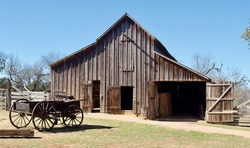 A wood barn and wagon at Lyndon B. Johnson State Park and Historic Site and the Sauer-Beckmann Farmstead, a living history farm in Stonewall, Texas. The farmhouse was built in the mid-1800s.