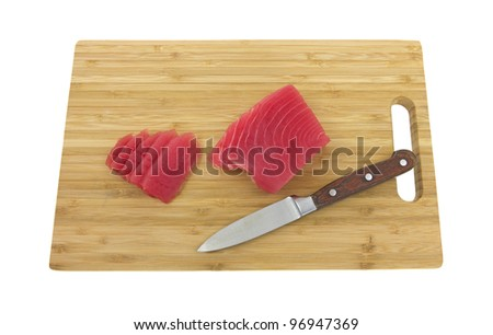 A wood cutting board with yellowfin tuna steak and slices on a white background. - stock photo