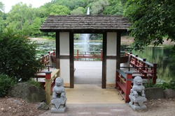 A wood pagoda leading to a viewing platform and seating area over a lake with a water fountain and surrounded by trees in Janesville, Wisconsin, USA