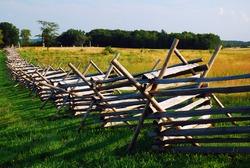 A wood split rail fence cuts through a field at Gettysburg National Battlefield