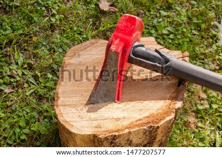 A wood splitting maul on top of a wooden log with grass in the background