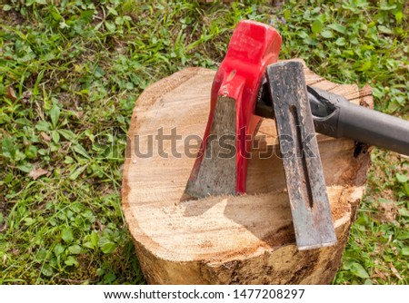 A wood splitting maul with a metal wedge on top of a wooden log with grass in the background