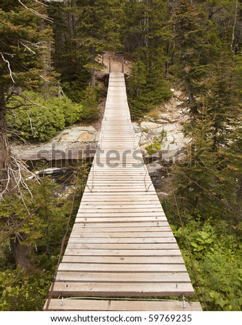 A wood suspension bridge provides a somewhat precarious crossing over a stream in Glacier National Park.