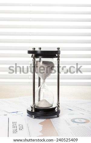 A wood working(office) table(desk) with sand timer(hour glass) on the graph paper(document)s for business behind blind(rolling blind, shade).