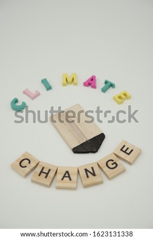 A wooden arrow with colored writing,climate change. Climate change concept