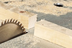 A wooden bar is sawn in half with a circular saw blade