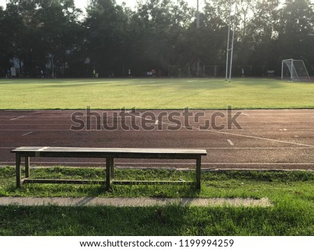 A wooden bench besides red rubber running track near the football field in the morning