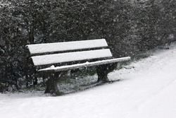 A wooden bench covered with snow during a blizzard