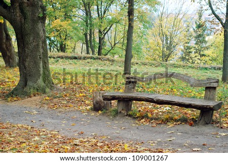 A wooden bench in a autumn park Stock Photo