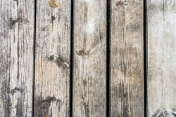 A wooden bench in front of a wood fence