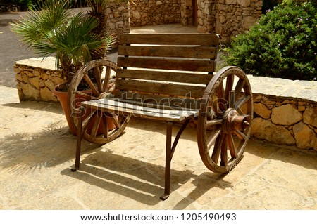 A wooden bench made using two wagon wheels