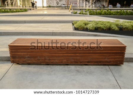 a wooden bench on concrete floor  #1014727339