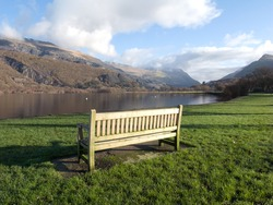 A wooden bench on green grass next to lake Padarn with a view of mountains in the Snowdonia national park, Wales, UK.