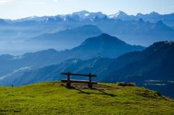 A wooden bench on top of the mountains of Rigi, Zwitserland with a beautiful view at the Alps