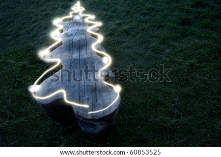 A wooden bench surrounded by grass at night.  An LED light has been used to trace the outline of the bench to make it look like a Christmas Tree.