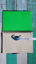 A wooden bird on a notebook with a green leaf. And the inscription