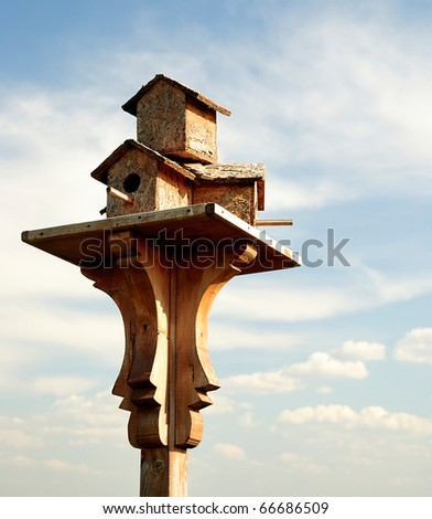 A wooden birdhouse on top of a pole with clouds in the background