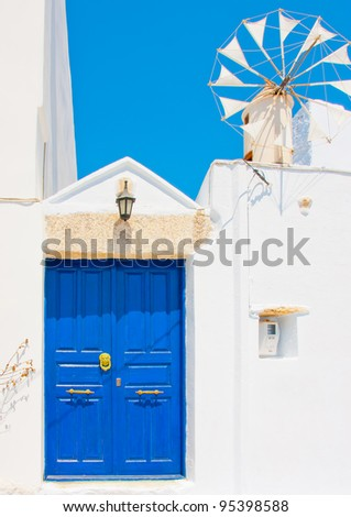A wooden blue colored door of a Beautiful traditional house in Chora the capital of Amorgos island in Greece. A small windmill exists beside